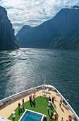 Norwegian Fjords Cruise. Passengers drinking cocktails a the bow of the TUI cruise ship Marella Explorer leaving Geiranger, Geirangerfjord, Norway ALMTT4B83| 写真素材・ストックフォト・画像・イラスト素材|アマナイメージズ