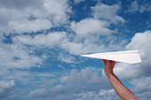 A man's hand holding a white paper airplane in a blue cloudy sky ALMBH3W67  写真素材・ストックフォト・画像・イラスト素材 アマナイメージズ