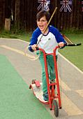 7 year old boy enjoying scooter ride at a summer fete, Sheet, Hampshire, UK. ALMDA44RG| 写真素材・ストックフォト・画像・イラスト素材|アマナイメージズ