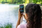 Germany, Bavaria, Allgäu, Füssen, woman taking picture of the Alpsee and Neuschwanstein Castle with mobile phone ALMWW7HW9  写真素材・ストックフォト・画像・イラスト素材 アマナイメージズ