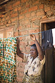 A woman hangs up washing outside her home in Kasese District, Uganda, East Africa. ALMG4XYME| 写真素材・ストックフォト・画像・イラスト素材|アマナイメージズ