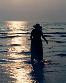 Silhouette of woman in dress and hat wading through the shallow water on an ocean beach in Florida at dusk ALMA7233T| 写真素材・ストックフォト・画像・イラスト素材|アマナイメージズ