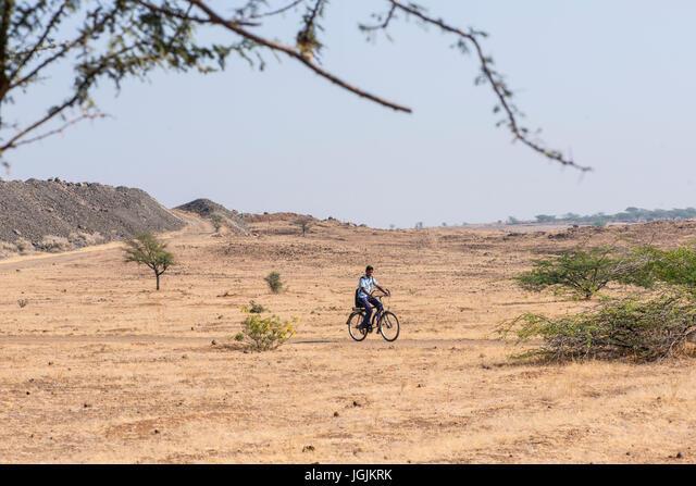 A village boy cycles to school via the Mayureshwar Wildlife Sanctuary in India ALMJGJKRK  写真素材・ストックフォト・画像・イラスト素材 アマナイメージズ