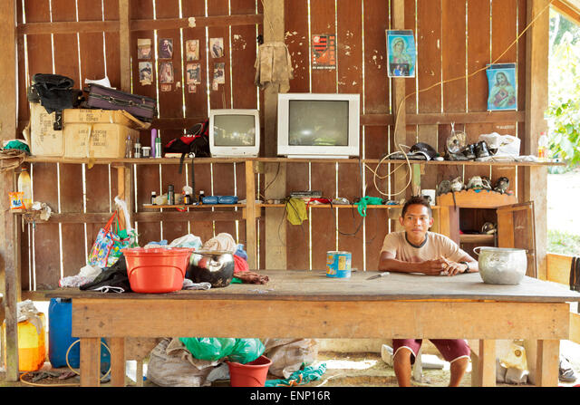 A young Satere boy in his family hut in the Brazilian rain forest surrounded by his worldy goods ALMENP16R  写真素材・ストックフォト・画像・イラスト素材 アマナイメージズ