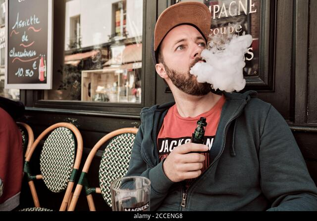 Europe, France, Paris, Montmartre, Sacre Coeur, Young man Smoking / Vaping at Street Cafe, ALM2CCENG8| 写真素材・ストックフォト・画像・イラスト素材|アマナイメージズ