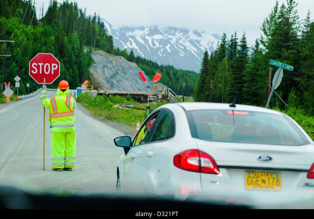Flagger, or flag person, stops traffic for construction on Highway 1 near Homer, Kenai Peninsula, Alaska, USA ALMD321PT  写真素材・ストックフォト・画像・イラスト素材 アマナイメージズ
