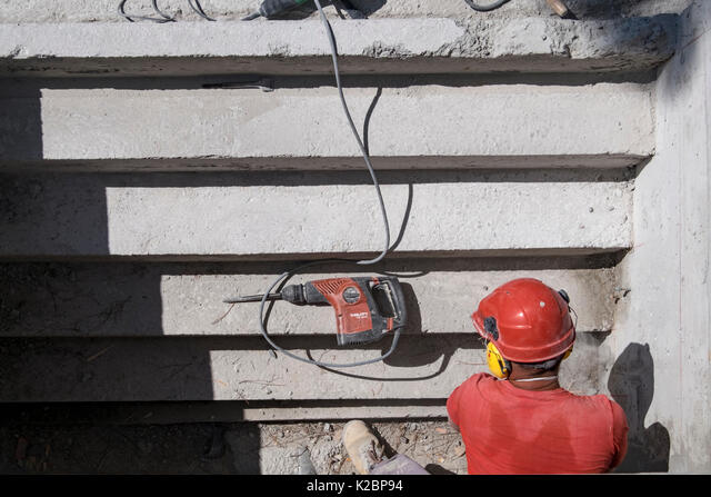 Construction worker wearing safety helmet and headphones uses a sander to sand the steps of a swimming pool ALMK2BP94  写真素材・ストックフォト・画像・イラスト素材 アマナイメージズ