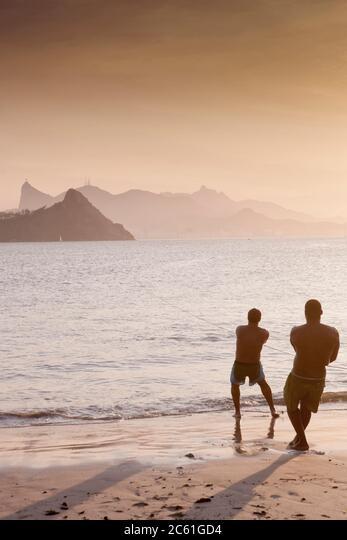 South America, Brazil, Rio de Janeiro, Niteroi. Fishermen pulling a net with the Rio skyline in the distance ALM2C61GD4| 写真素材・ストックフォト・画像・イラスト素材|アマナイメージズ