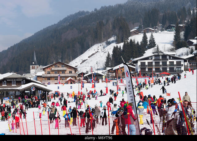 French Ski School, Chalet Accommodation and Shops at The Lower Skiing Area at Les Gets near Morzine with Skiers and Snowboarders Haute Savoie France ALMM6YT96  写真素材・ストックフォト・画像・イラスト素材 アマナイメージズ